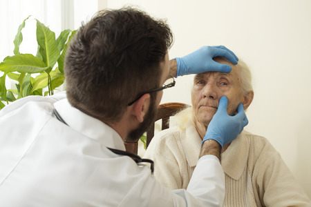 geriatrician: The doctor examines the eyes, conjunctival very old woman