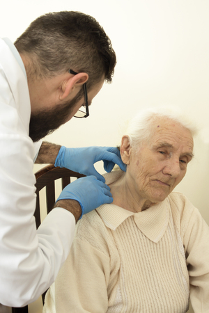 geriatrician: The doctor geriatrician during the test. Doctor examines changes in the skin of an old woman.