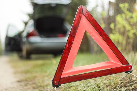 A broken car on the side. Warning triangle