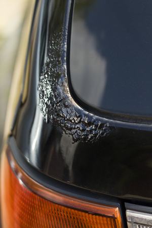 corrosion: Corrosion on the black car lacquer on the trunk latch. Stock Photo
