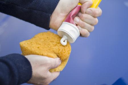 メカニックの手は、スポンジに研磨ペーストを適用します。 写真素材