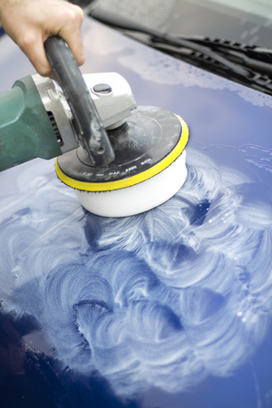 The hands hold an electric polisher and polish the lacquer on the cars bonnet. Banco de Imagens