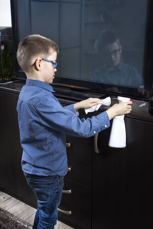 The boy cleaning the room. He applies detergent for furniture with an applicator. In the other hand, he holds a white wiping cloth.