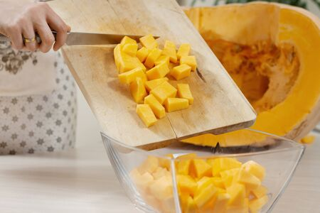 woman in a kitchen apron transfers the diced pumpkins from a wooden chopping board onto a glass plate.