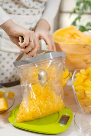Woman spreads a tablespoon of grated fresh pumpkin wrapped in a plastic bag.