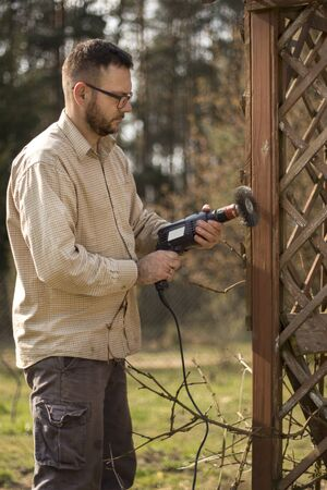Man with glasses and a flannel shirt during spring gardening. Renovation and maintenance of garden pergolas. Removing old paint from wooden elements. Foto de archivo