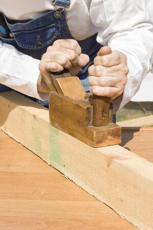 Hand plane. An employee plane the board. The construction worker boards the timber through a manual plane.