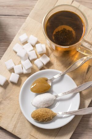 Lump sugar, cane sugar, loose white sugar and buckwheat honey on a teaspoon lie next to a glass with brewed herbal infusion.