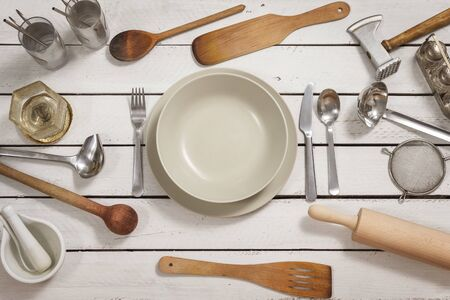 Place setting for one person prepared on a wooden table made of white boards. Old stylish kitchen utensils are spread out around. The whole creates an interesting background.