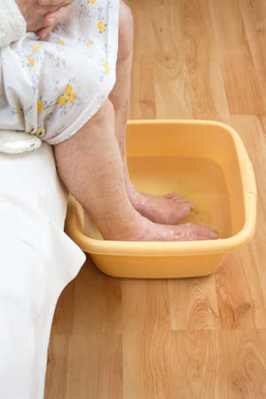 Old woman soaking feet in a bowl of water. The legs of an old woman soak in a bowl of water.