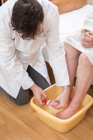 The male nurse scrubs the feet of an old woman who is soak feet in a bowl of water.