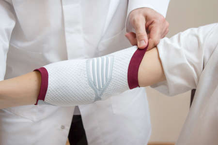 An orthopedic surgeon in a white coat assumes a stabilizer on the woman's elbow.