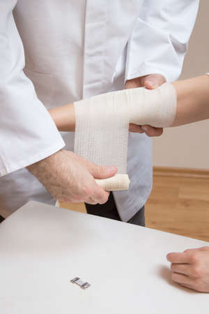 The doctor puts a dressing from the bandage on the woman's forearm.