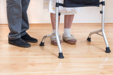 Legs of a very old woman in white socks and slippers. The old lady learns to walk with the help of a rehabilitation walker. The legs and feet of an old woman with the wheels of the walke
