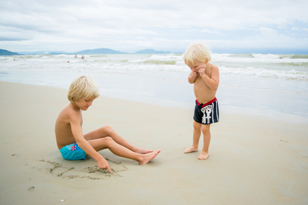 Two blond brothers playing in sand near the sea water at a beach