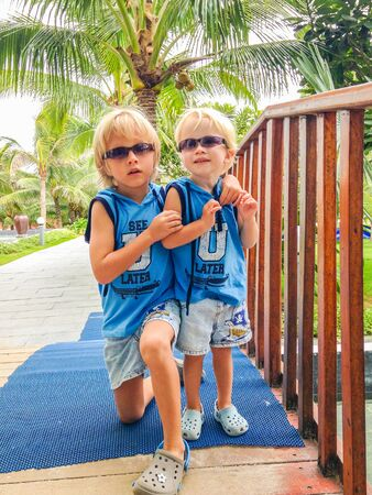 two brothers in the same sunglasses and clothes at a tropical resort, Vietnam