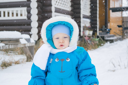 Baby boy walking at a snow yard - winter outing