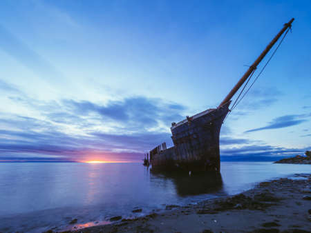 Abandoned wrecked sailboat in shallow water of sea near coastline on background of colorful sunset sky LANG_EVOIMAGES