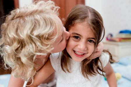 Boy kissing cheek of sister