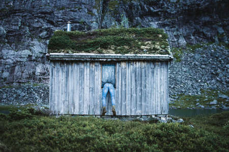 Back view of man sticking out of window of small old cabin in rocky mountains
