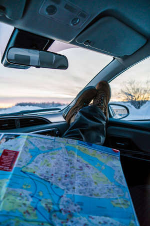 Unrecognizable person sitting and resting with map in car in the winter