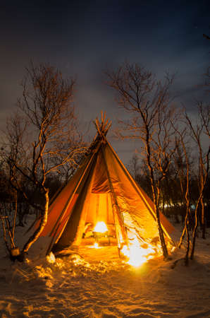 Tent with bonfire inside and frosted forest covered with snow at night