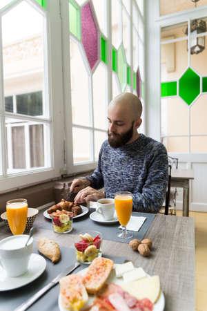 Vertical indoors shot of man having fresh orange juice breakfasting in the cafe