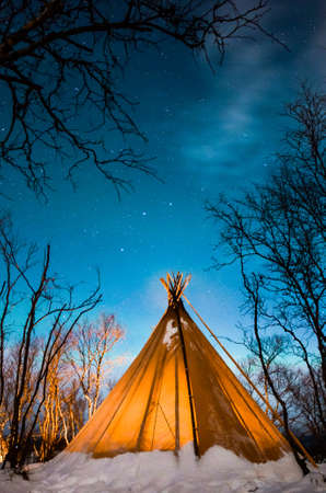 View to tent placed in snowy winter forest at night LANG_EVOIMAGES