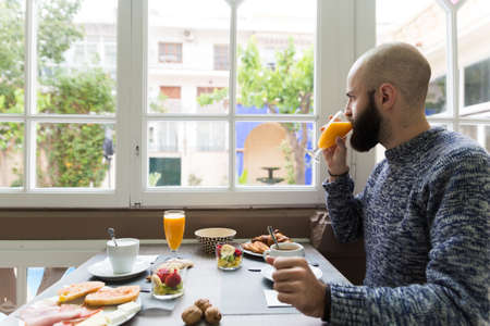 Horizontal indoors shot of man having fresh orange juice breakfasting in the cafe LANG_EVOIMAGES