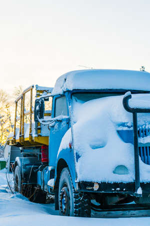 View to blue truck covered with snow in winter day