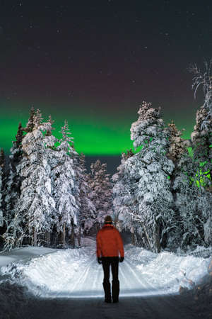 Back view of tourist man standing on road in winter forest at night with Polar light