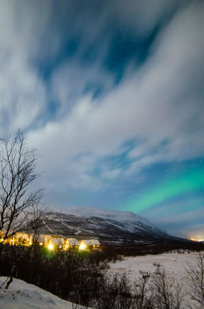 View to light small northern village under cloudy sky in winter night LANG_EVOIMAGES