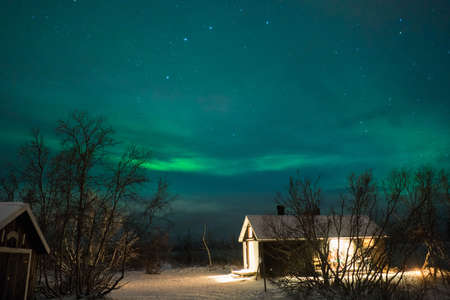 View to northern house with light at winter night with Polar light
