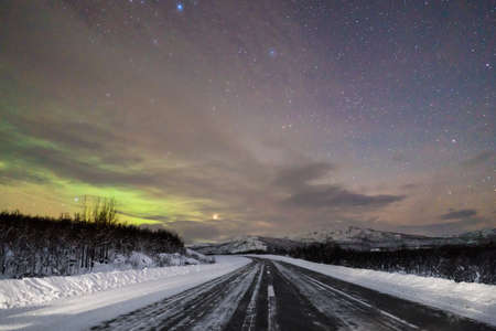 Perspective view to asphalt road and nature covered with snow in winter night