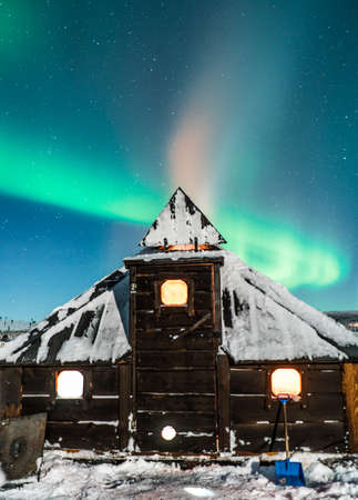 View to light house covered with snow and winter night with Polar light LANG_EVOIMAGES