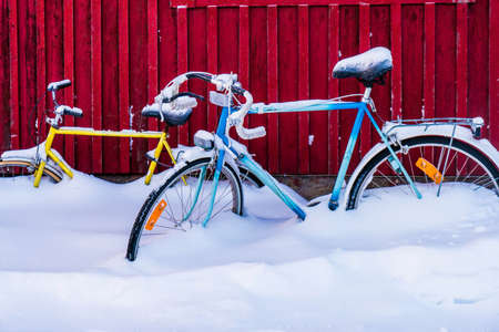 Two bicycles parked in snow at the fence in cold day