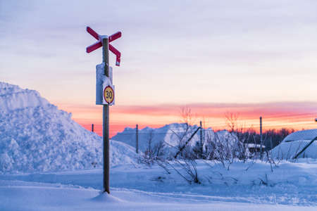 View to railroad signpost placed in snow in winter evening
