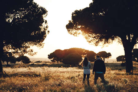 Romantic back view of a couple walking in the field at sunset in Madrid, Spain