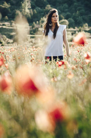 Young woman posing in the middle of a field of poppies in the countryside in Madrid, Spain LANG_EVOIMAGES