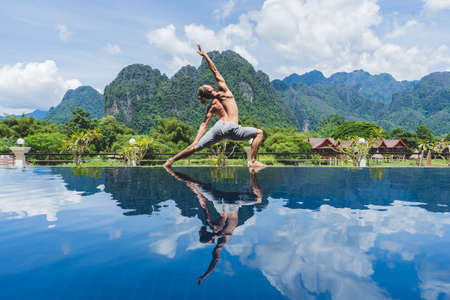 Anonymous shirtless man posing in yoga on poolside with tropical resort in mountains on background