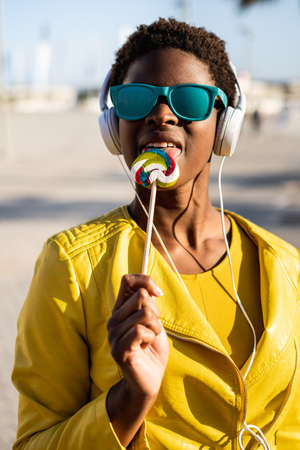 African American woman in sunglasses in yellow jacket enjoying a lollipop and listen to music on headphones Фото со стока - 133259750