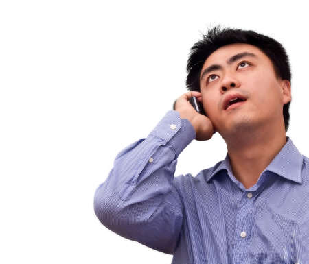 An asian business man looking up to check information while talking on the phone photo