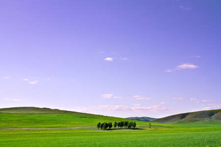 Landscape photo of a farm grass plain in a moutain area under blue sky Stock Photo