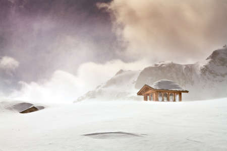 Landscape photo of Wooden cottage and snow covered huts in blizard at the peak of snow mountain
