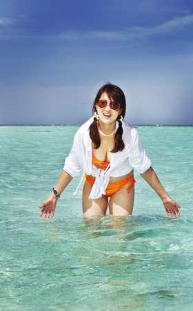 A beautiful fashion asian girl playing water in Maldive beach near the ocean in the hot summer Stock Photo
