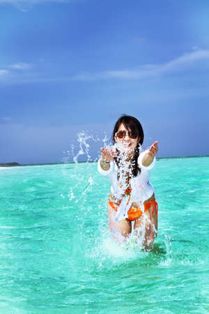 A beautiful fashion asian girl playing water in Maldive beach near the ocean in the hot summer photo