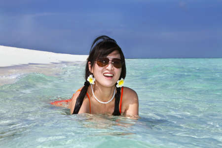 A beautiful fashion asian girl playing water in Maldive beach near the ocean in the hot summer Stock Photo