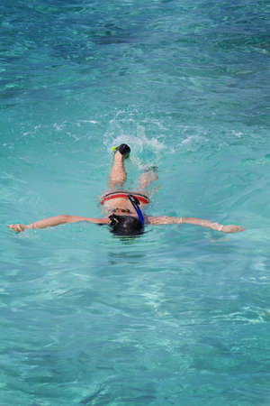 Photo of beautiful asian girl snorkeling in crystal clear Maldive waters with ripples. Stock Photo - 14033371
