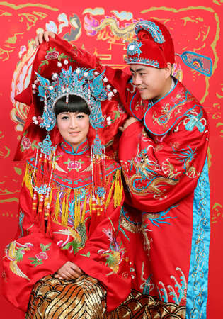 Closeup photo of Chinese young couple dressed in traditional wedding suite in typical Chinese wedding ceremony Stock Photo