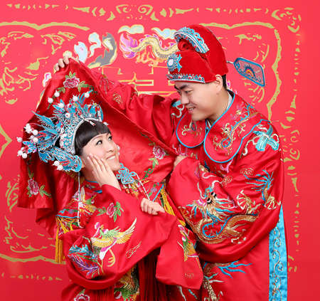 Closeup photo of Chinese young couple dressed in traditional wedding suite in typical Chinese wedding ceremony Reklamní fotografie